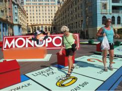 Shirley Theal, center, and Pat Wilson, both of Niagara Falls, Canada, walk on a life-sized Monopoly board on the Boardwalk in Atlantic City.