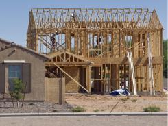 Builders frame a new home behind a finished new home in Queen Creek, Ariz.