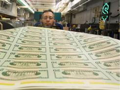 Jose R. Del Toral inspects stacks of freshly made $20 bills at the Bureau of Engraving and Printing in Washington.