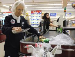 Cashier Joyce Mackie bags groceries as a customer uses a self-serve checkout station at a Big Y supermarket in Manchester, Conn.