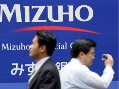 Japanese businessmen pass by the headquarters of the Mizuho Financial Group in Tokyo.