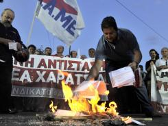 Protesters burn their emergency tax notes during a rally in front of the finance ministry in Athens.