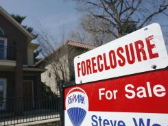In this 2010 file photo, a foreclosure sign sits atop a for sale sign in front of a single-family home in Denver.
