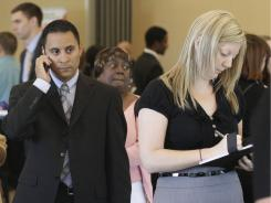 Lorenzo Ortiz, and Annelie Ingvarsson, right, wait to talk to potential employers during a National Career Fairs job fair, in Bellevue, Wash. Sept. 24, 2011.