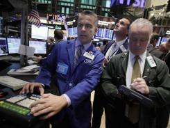 Specialist Christopher Culhane, left, at his post Tuesday on the floor of the New York Stock Exchange.