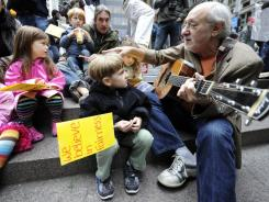 "Peter Yarrow of the folk group ""Peter Paul and Mary"" plays a song at New York's Wall Street protest as Desmond Keller of Brooklyn listens."