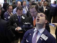 Specialist Michael Gagliano, foreground right, calls out prices at his post Tuesday on the floor of the New York Stock Exchange.