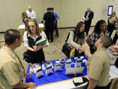 Navy recruiters greet job seekers during a job fair sponsored by the California Job Journal in South San Francisco, Calif.