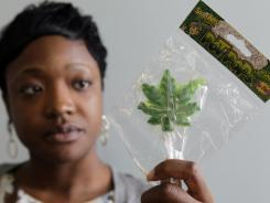 "Felicia Williams, Community Liaison for Buffalo City Council member Darius Pridgen, holding a ""Pot Pop"" lollipop in Buffalo, N.Y."