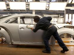 An employee checks alignment of body panels on VW's new generation Beetle at a    plant in Puebla state, Mexico.