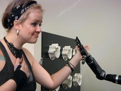 Katie Schaffer gets a high-five from her boyfriend Tim Hemmes's mechanical prosthetic arm at the University of Pittsburgh Medical Center.