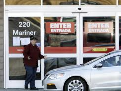 A customer is puzzled after trying to enter a closed Lowe's store in Biddford, Maine, on Monday.