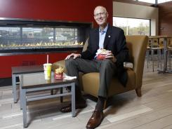 Wendy's CEO Emil Brolick sits in the dining area of a Wendy's in Columbus, Ohio. It has comfortable chairs, a fireplace and a big screen TV.