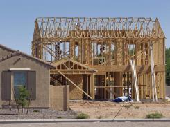 In this Aug. 22, 2011 photo, builders frame a new home behind a finished new home in Queen Creek, Ariz.