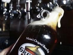 In this Monday, Oct. 3, 2011 photo, a growler is filled at the bar at Gritty McDuff's in Portland, Maine.