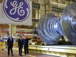 GE CEO Jeffrey Immelt, left, and plant manager Kevin Sharkey, right, give President Barack Obama a tour of a GE plant in Schenectady, N.Y.