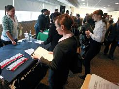 Job seekers crowd tables to get information and drop off resumes during a job fair in Boston Oct. 17, 2011.