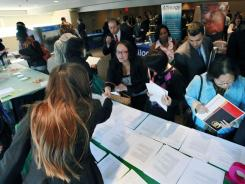 Job seekers crowd around tables to get information and drop off resumes during a job fair in Boston Oct. 17.