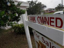A bank-owned sign in front of a foreclosed home Oct. 13, 2011 in Miami.