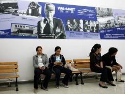 Customers under a picture of Sam Walton, founder of Wal-Mart, at a Beijing Walmart store.