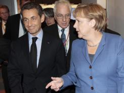 French President Nicolas Sarkozy and German Chancellor Angela Merkel arrive Sunday at a news conference at the EU summit in Brussels.