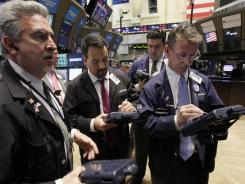 In this Oct. 11, 2011 photo, traders work on the floor of the New York Stock Exchange.