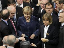 German Chancellor Angela Merkel, center, waits to cast her ballot at the German federal parliament in Berlin Wednesday.