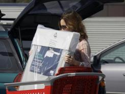 A shopper loads purchases into her car at a mall in Culver City, Calif., Sept. 29, 2011.