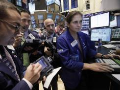 In this Oct. 27, 2011 photo, specialist Jennifer Klesaris, right, works at her post on the floor of the New York Stock Exchange.
