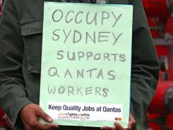 "An ""Occupy Sydney"" protester holds a placard as the group stages a demonstration outside the venue of the Qantas annual general meeting."