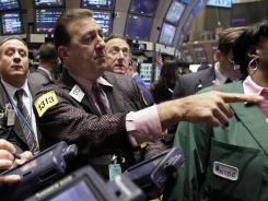 In this Oct. 12, 2011 file photo, Stephen Holden works on the floor of the New York Stock Exchange with fellow traders.