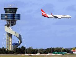 A Qantas jet prepares to land Monday at Sydney Airport in Sydney. Qantas Airways planes returned to the skies after a court ruling.
