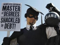 "Gan Golan, of Los Angeles, dressed as the ""Master of Degrees,"" holds a ball and chain representing his college loan debt, during Occupy DC activities in Washington."