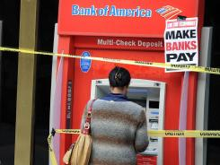 Customers use Bank of America ATM machines in Los Angeles  after protestors cover the machines with yellow danger tape and protest signs during an anti-Wall Street demonstration.