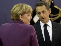 French President Nicolas Sarkozy speaks with German Chancellor Angela Merkel upon arriving for the summit in Cannes, France, on Wednesday.