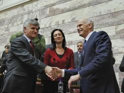 Greek Prime Minister George Papandreou, right, shakes hands Thursday with Socialist members of parliament prior his speech in Athens.