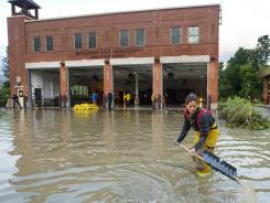 Firefighter Mandy Drake clears a storm drain in front of the Waterbury Fire Department in the wake of tropical storm Irene in August 2011.  The building was evacuated as high water from the Winooski River flooded downtown.