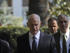 Greece's Prime Minister George Papandreou exits the Presidential house after meeting with Greek President Karolos Papoulias, in Athens, on  Saturday.