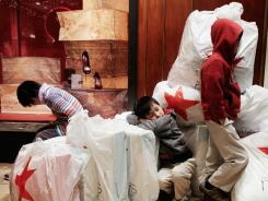 "Children wait with shopping bags inside Macy's department store on ""Black Friday"" on Nov. 26, 2010 in New York City."