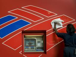 An ATM machine across the street from Bank of America's Charlotte headquarters is cleaned.