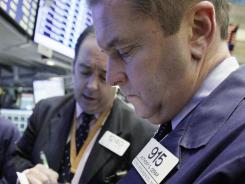 In this Nov. 7, 21011 photo, trader Anthony Cerar, right, works on the floor of the New York Stock Exchange.
