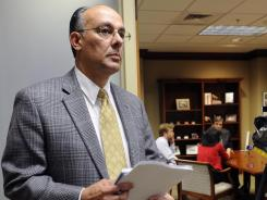 County manager Tony Petelos stands outside a room as Jefferson County Commission President David Carrington holds a news conference in his office.
