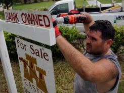 Renzo Salazar, from Real Signs of Ace Post Holding, places a bank owned sign on top of a for sale sign in front of a foreclosed home on October 13, 2011 in Miami, Florida.