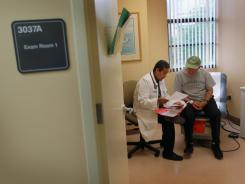 Dr. Olveen Carrasquillo sits with Juan Gonzalez as he conducts a checkup at the University of Miami Miller School of Medicine on Jan. 18, 2011.