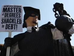 Gan Golan of Los Angeles  holds a ball and chain representing his college loan debt during Occupy DC activities in Washington.