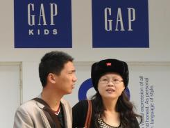 Shoppers on Oct. 21 walk past a Gap clothing store in Beijing.