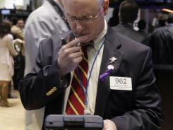 In this Nov. 10, 2011 photo, trader Kevin Cassidy works on the floor of the New York Stock Exchange.