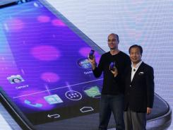 Google executive Andy Rubin, left and J.K. Shin of Samsung, hold the new Galaxy Nexus smartphone, which uses Android software, at an Oct. 19 event.