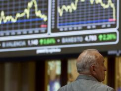broker looks at the Stock Exchange screen in Madrid on  Aug. 8, 2011.