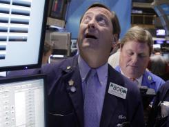 Trader Christopher Drummond, left, works on the floor of the New York Stock Exchange, Thursday, Nov. 17, 2011.
